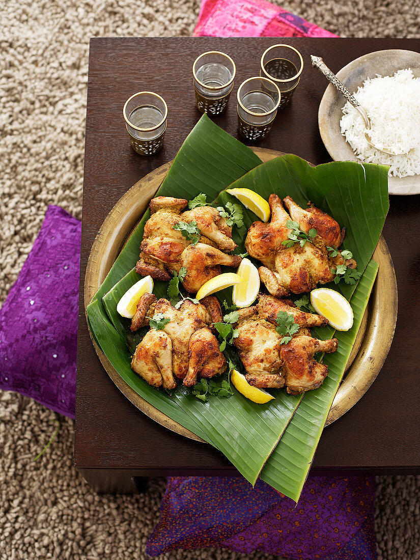 A spring chicken with coriander and lemon wedges on a banana leaf