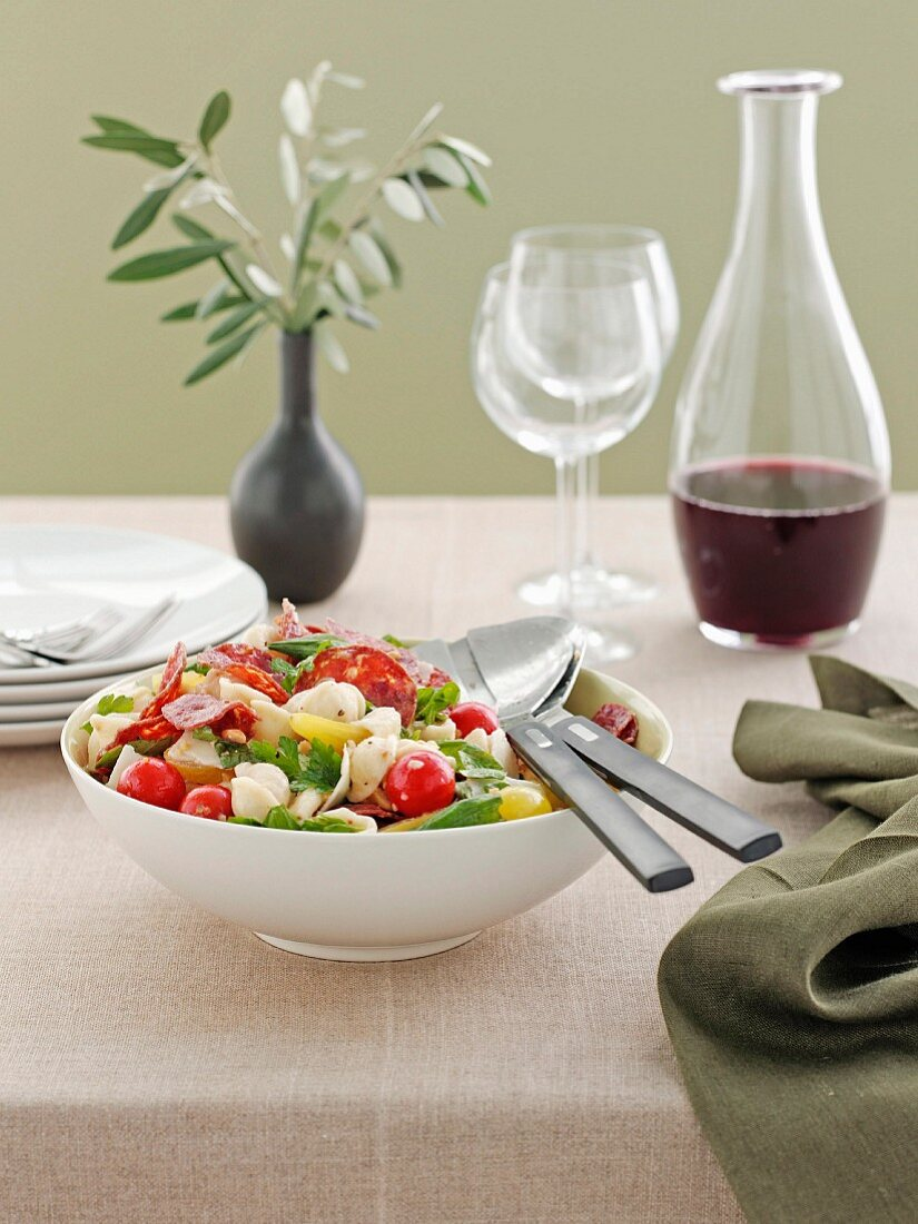Warm pasta salad with salami and tomatoes