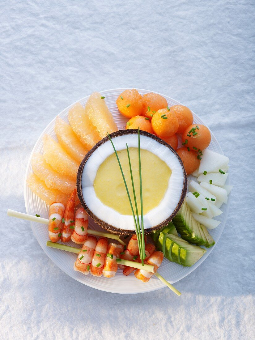Prawn kebabs with fruit and melon sauce in a coconut shell
