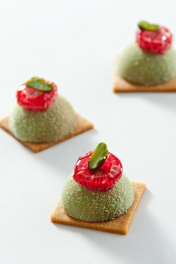 Petit fours with pistachios and raspberry icing