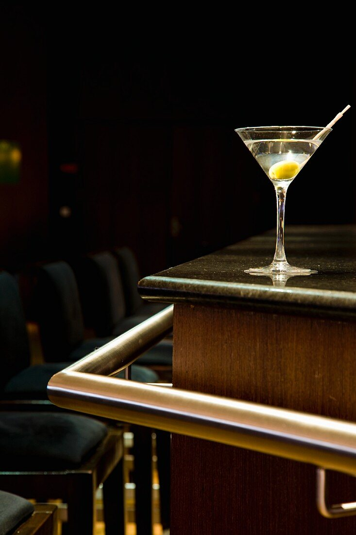 A martini with an olive on a bar