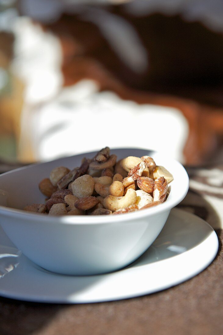 A selection of nuts in a white porcelain bowl on a plate