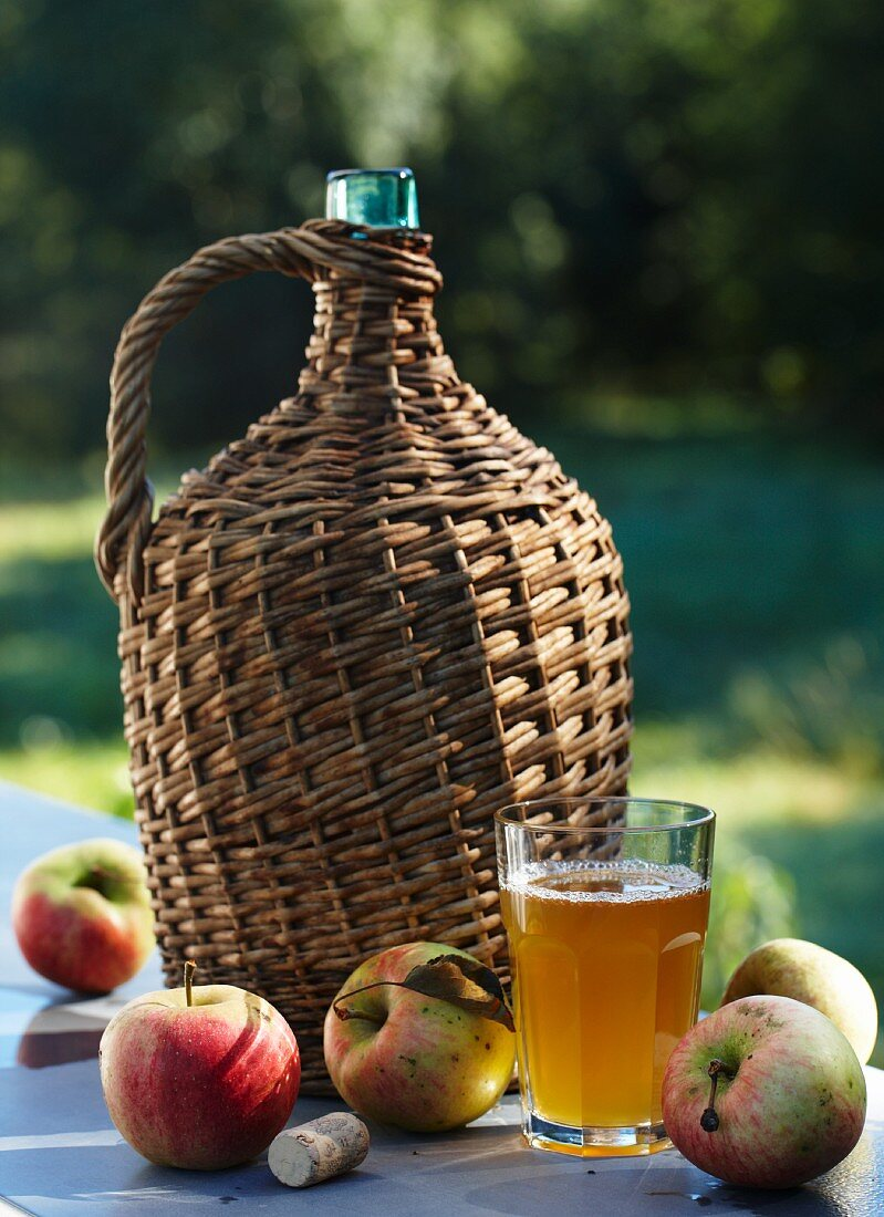 Apple must in a demijohn, a glass of apple juice and fresh apples