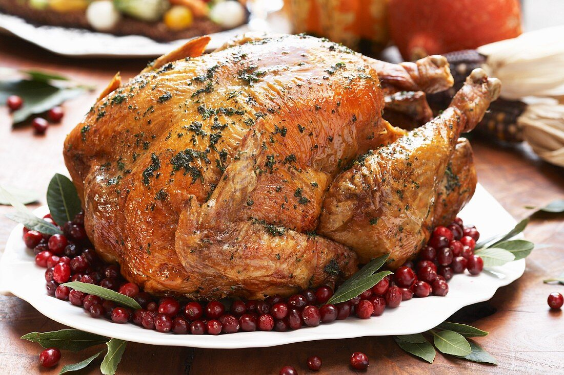 Whole Roast Turkey on a Platter with Cranberries and Bay Leaves