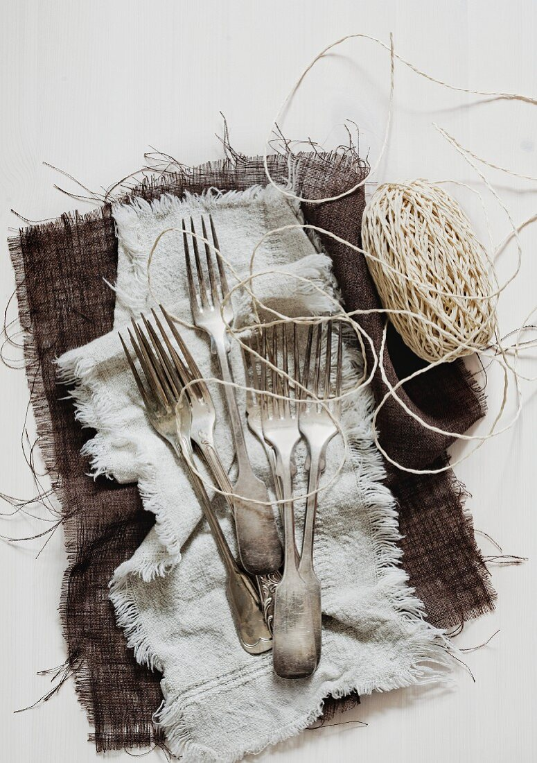 Old forks and kitchen twine on cloth