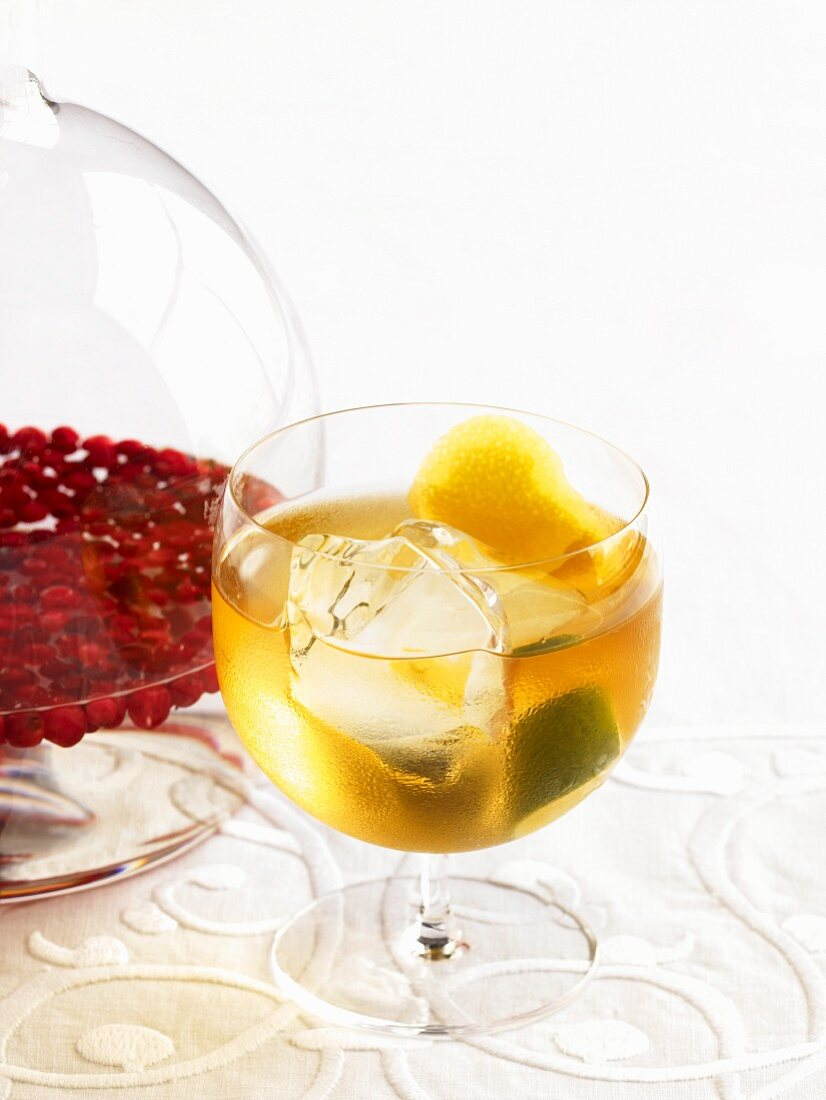 Glass of Lemon Lime Nastoyka (Russian Infused Vodka) With a Pitcher of Lingonberry Nastoyka