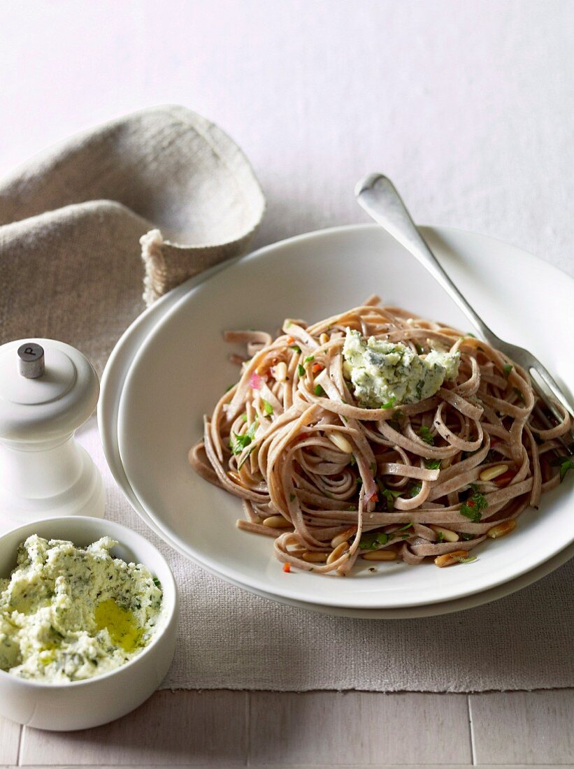 Spelt fettuccine with herb cream cheese and pine nuts