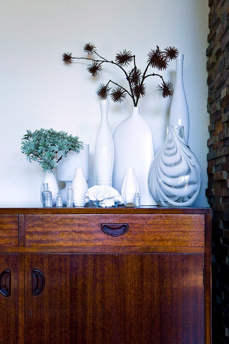 Dried flowers in a collection of vases on a sideboard