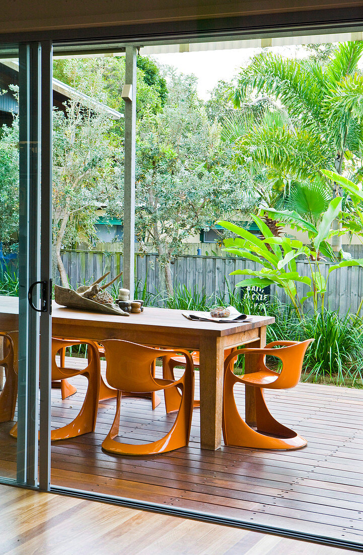 A solid wooden table with orange plastic chairs on a wooden terrace