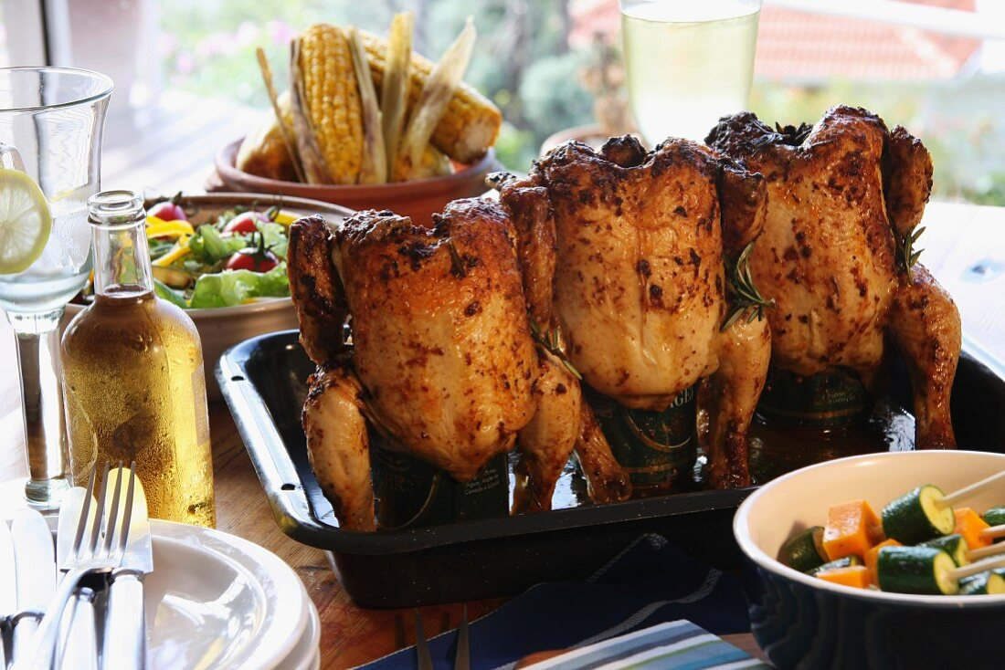 Beer can chicken, vegetables and corn cobs