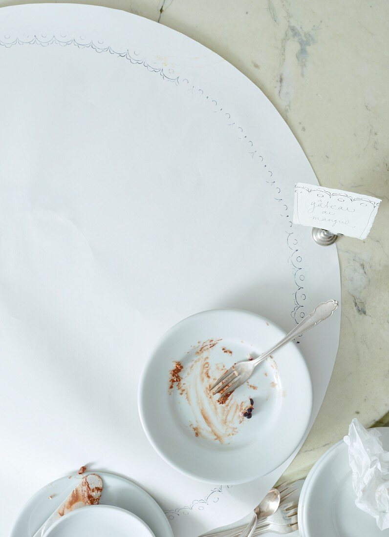 A cake plate with crumbs on a bistro table (seen from above)