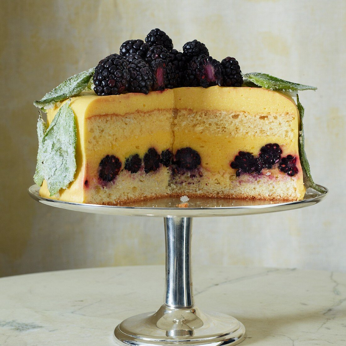An orange and basil cake with blackberry, sliced