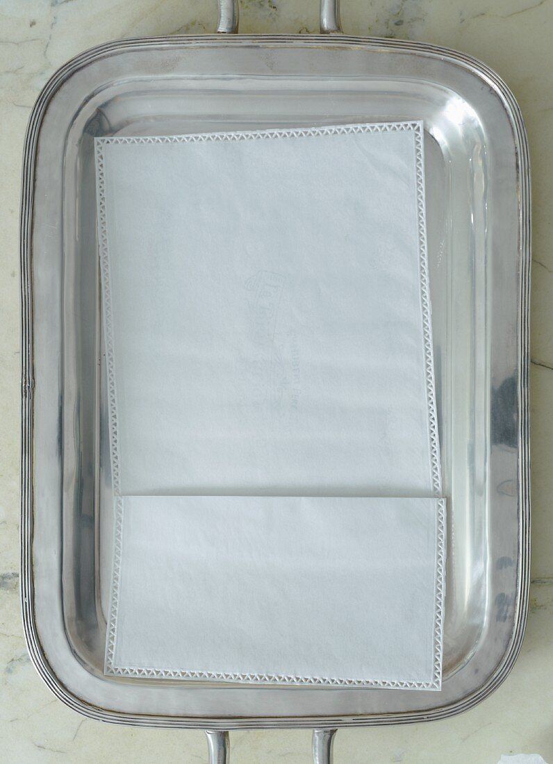 A napkin on a silver tray on a marble table