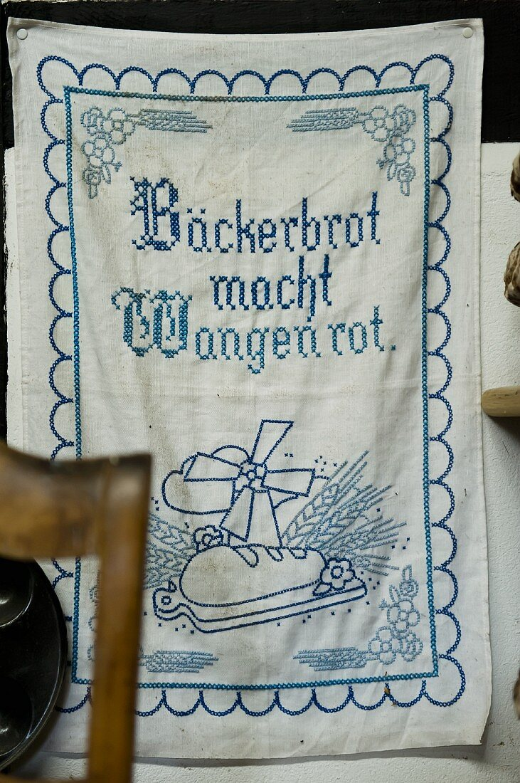 A tea towel with a proverb hanging on a wall