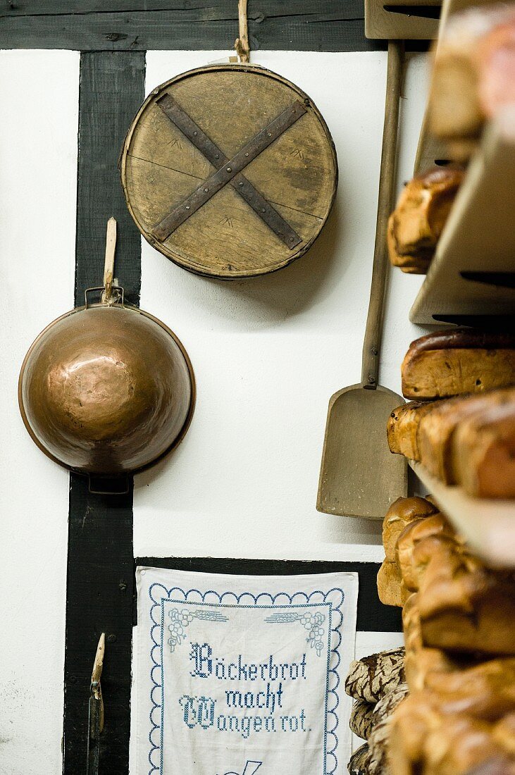 Various utensils next to a bread shelf in an old bakery