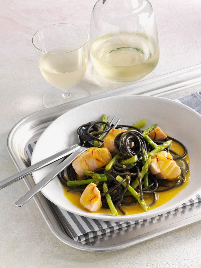 Squid ink pasta with salmon and Thai asparagus in a saffron sauce