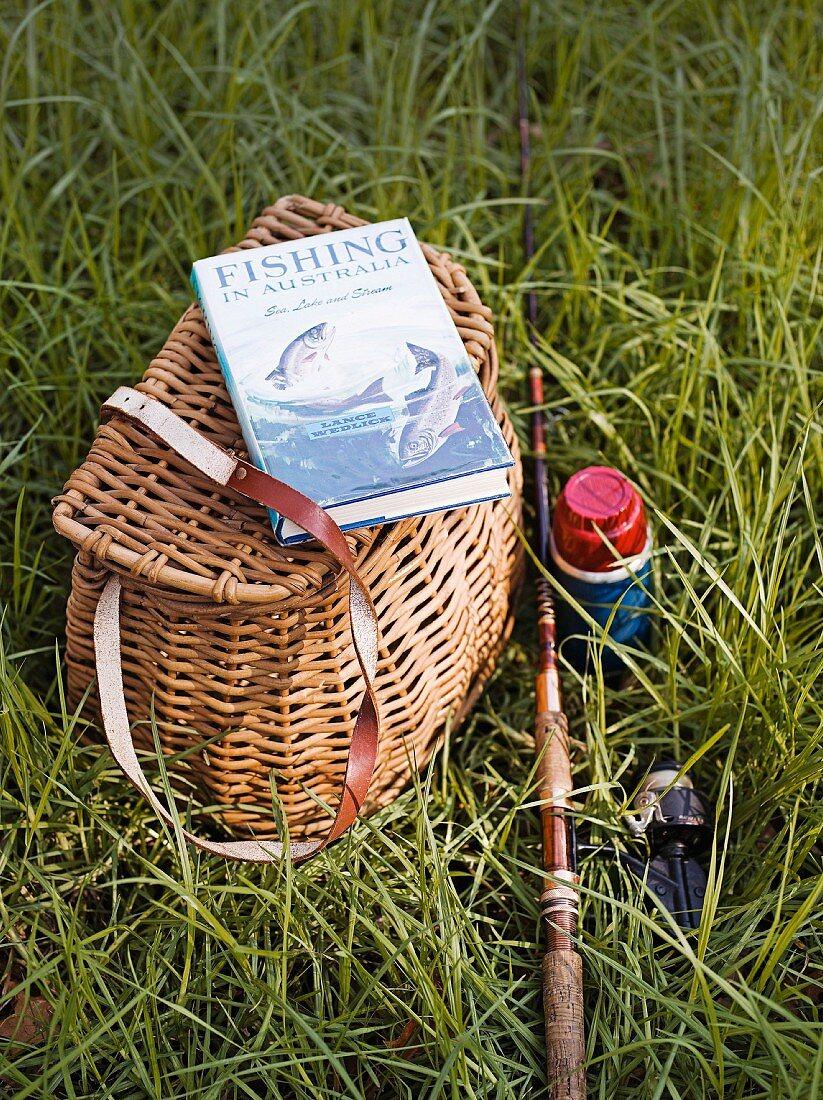 Fischerkorb, Buch und Angelrute auf der Wiese