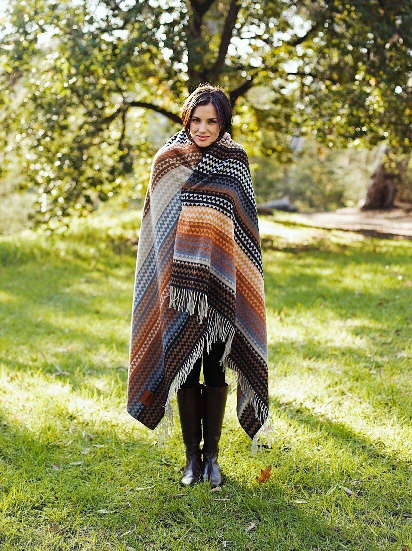 Junge Frau steht in Decke gewickelt auf einer Wiese