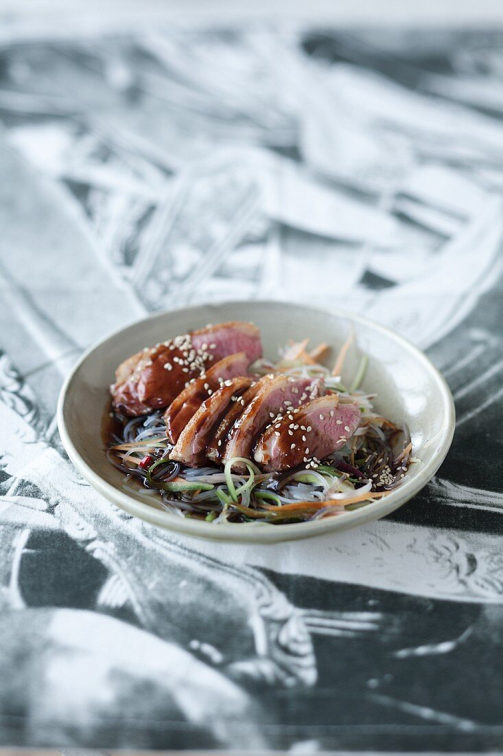 Duck breast on a bed of glass noodles with teriyaki sauce