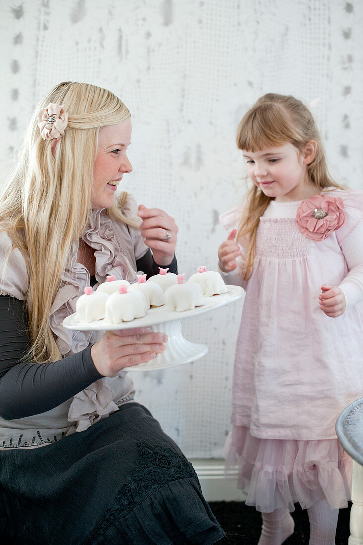 A mother dressed for a celebration, with her young daughter, holding a cake stand of mini birthday cakes in her hand