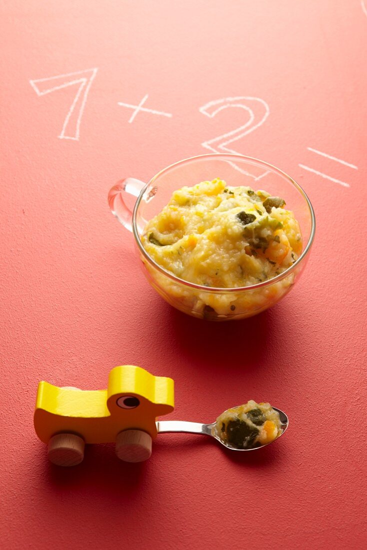 Vegetable baby food in a glass cup next to a toy duck