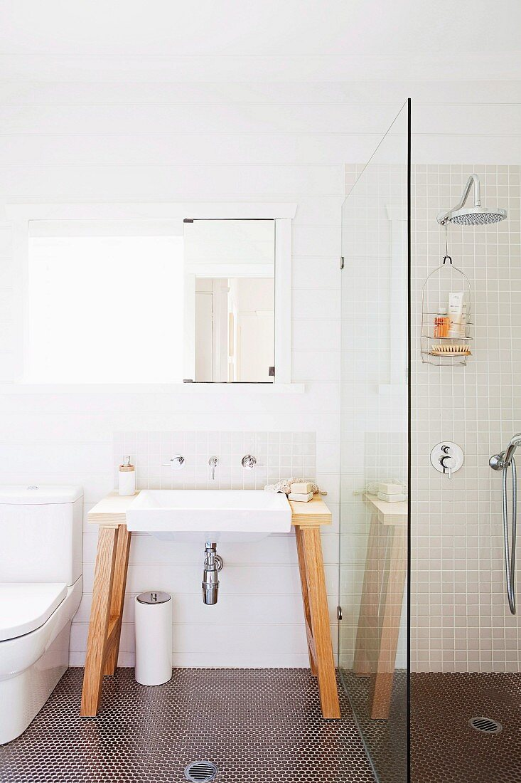 Free standing vanity with wall faucet and mirror next to a shower partition