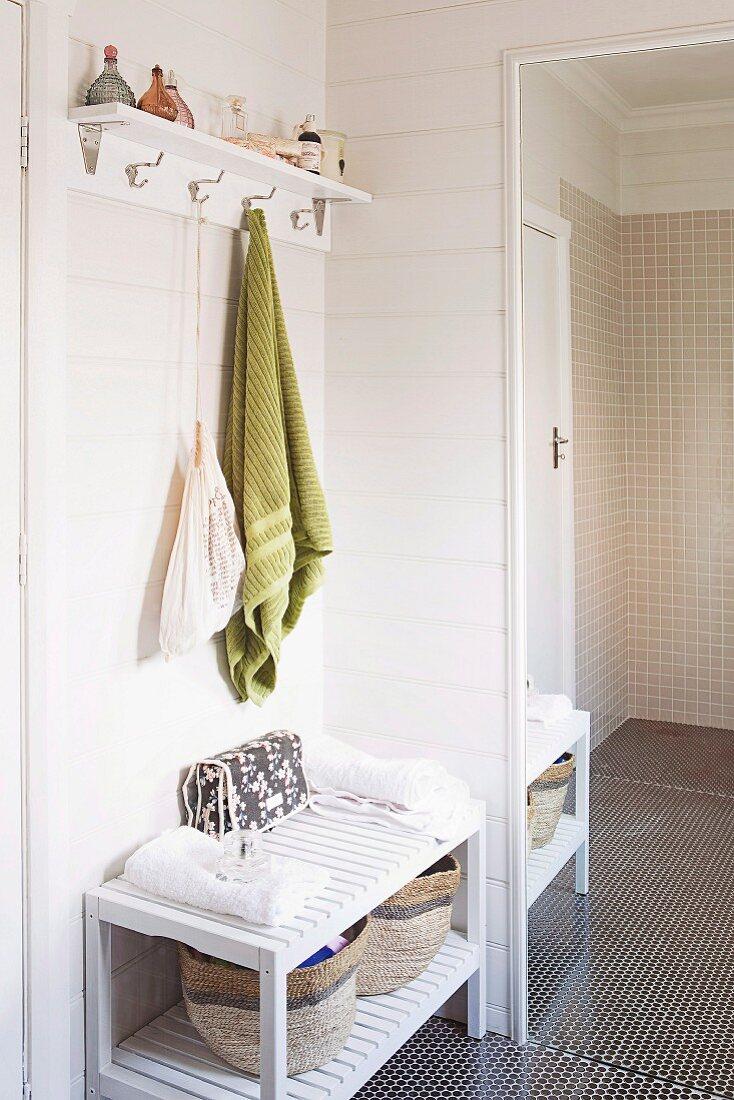 Badezimmerecke mit grünem Handtuch an Wandhakenleiste über halbhohem Regal neben Ganzkörperspiegel
