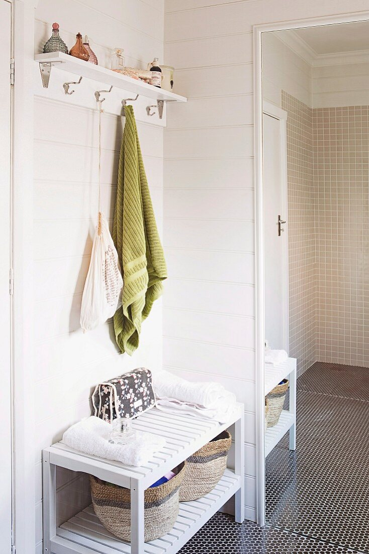 Corner of a bathroom with a green hand towel hanging from a wall shelf with hooks next to a full length mirror