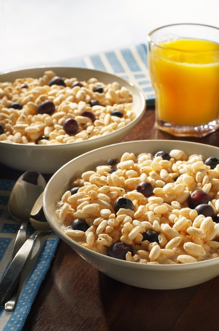 Two Bowls of Puffed Rice Cereal with Fresh Blueberries and Orange Juice