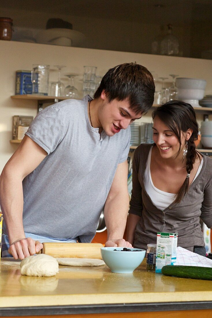 A young couple making pizza