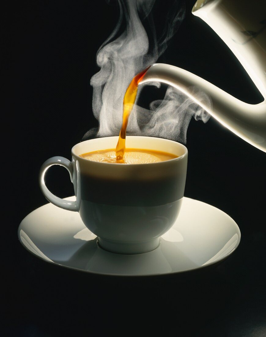 A cup of coffee being poured against a black background