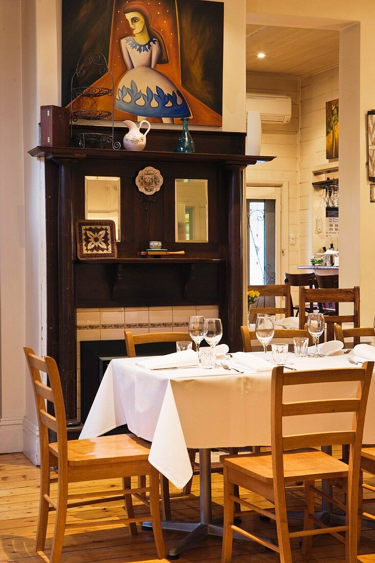 Restaurant tables in front of an open fireplace with antique wood surround and a modern painting above it