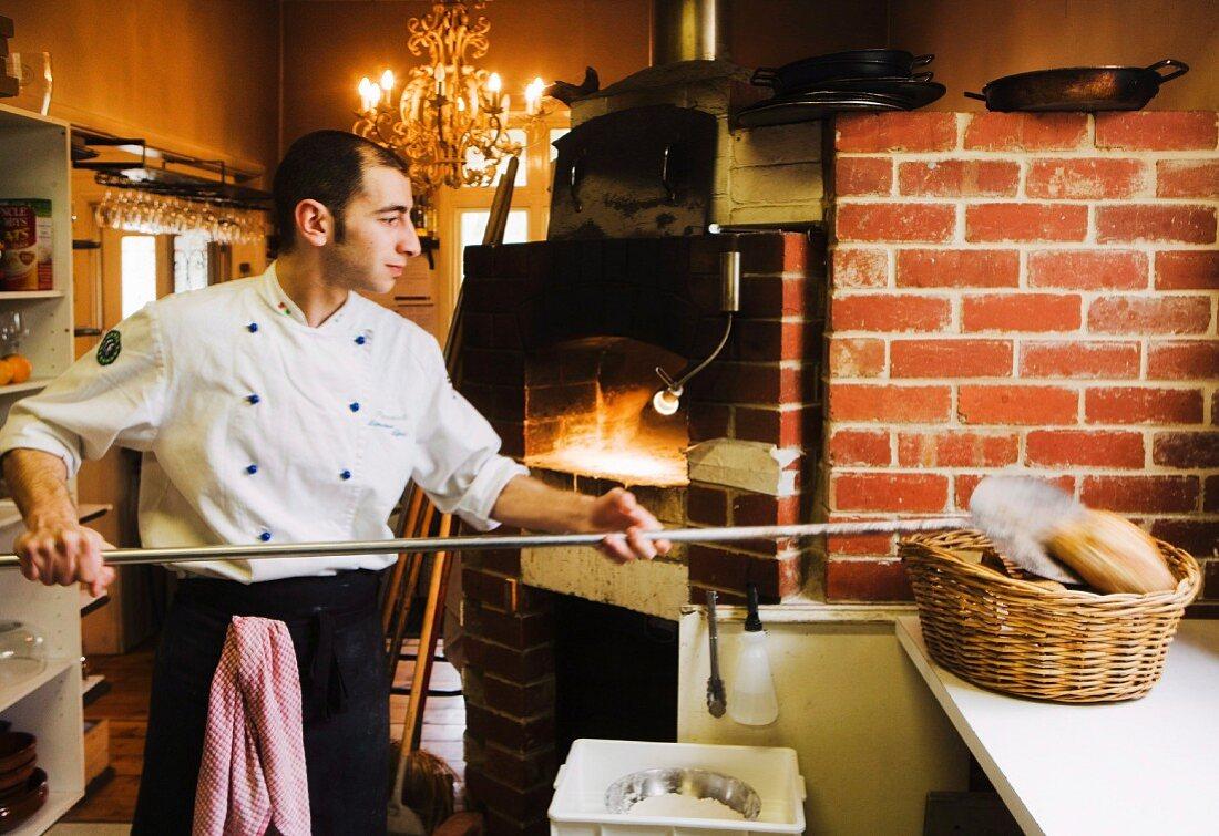 A baker placing a freshly baked loaf in a basket
