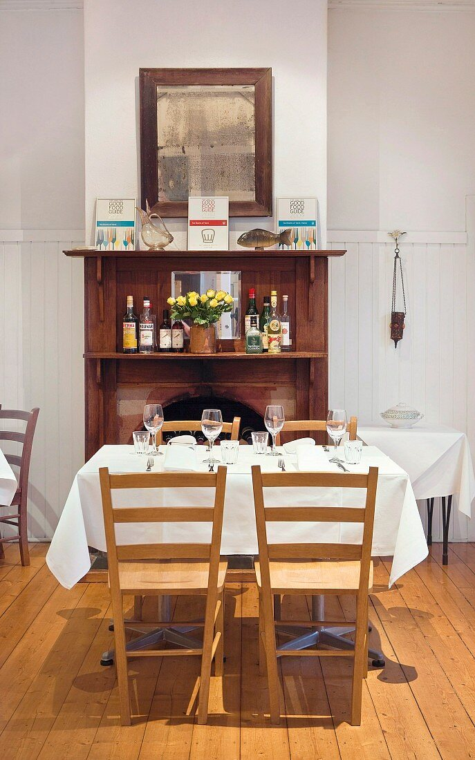 Set table in a restaurant; in the background an open fireplace with a wood surround and an antique wall mirror above it
