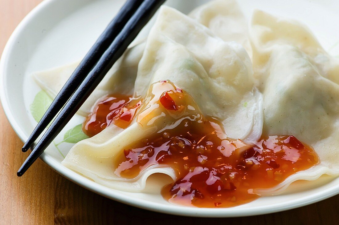 Steamed Dumplings with Red Chili Sauce on a Plate with Chopsticks
