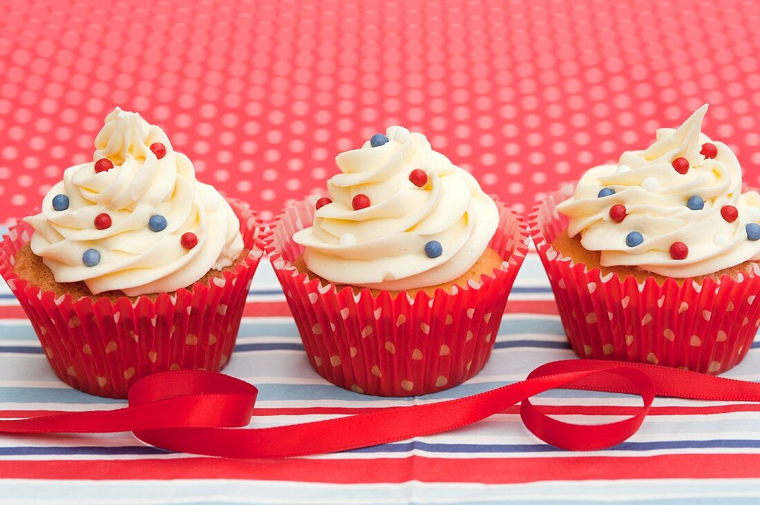 Three decorative cupcakes with a red ribbon
