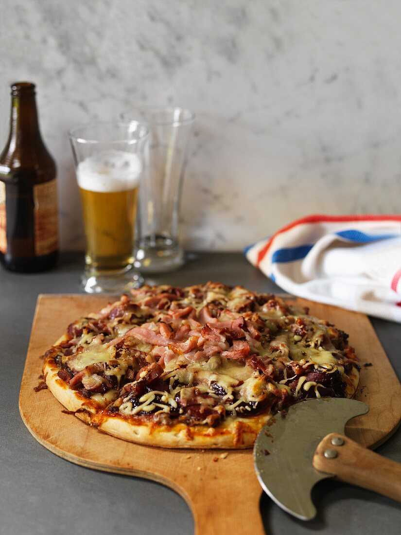 Ham, minced meat and cheese pizza with beer
