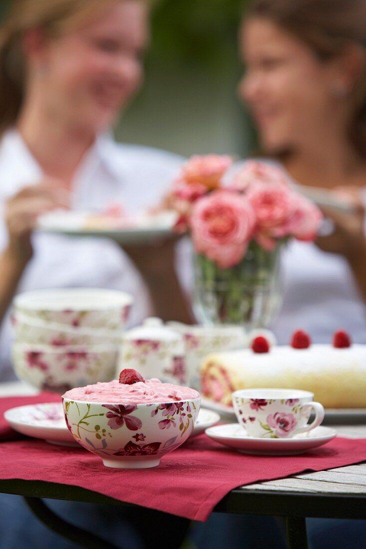 Raspberry Swiss roll and raspberry cream a garden table
