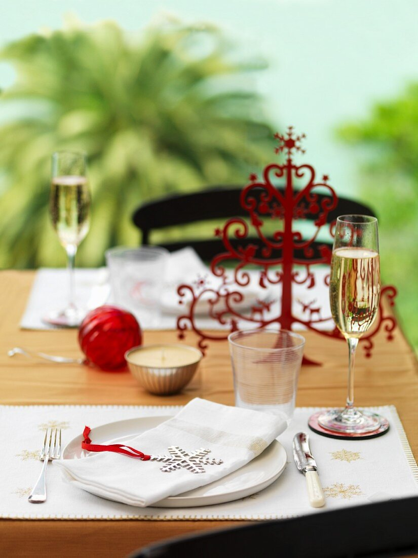 A Christmas place setting with champagne glasses