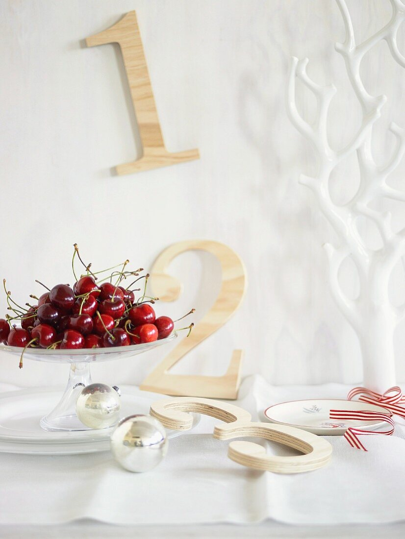 Fresh cherries, Christmas baubles and decorative wooden numbers