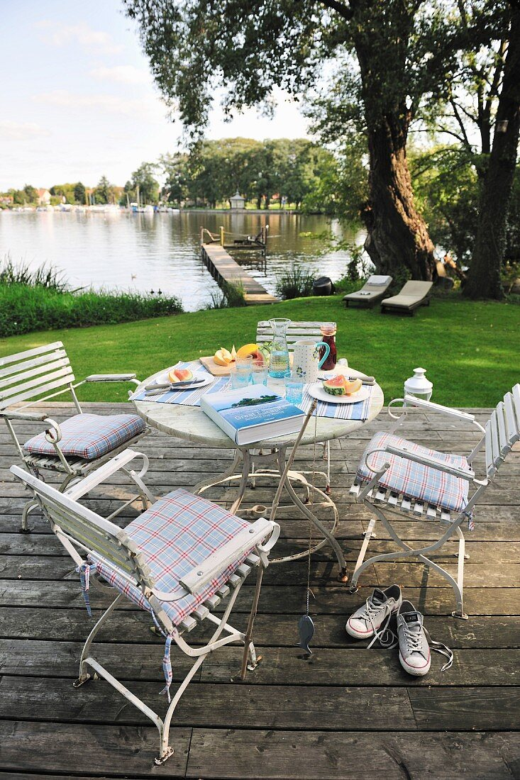 Dining area on a terrace - white chairs and table on a wooden deck with a view of a pond