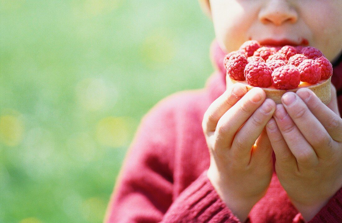 A child eating a raspberry tartlet