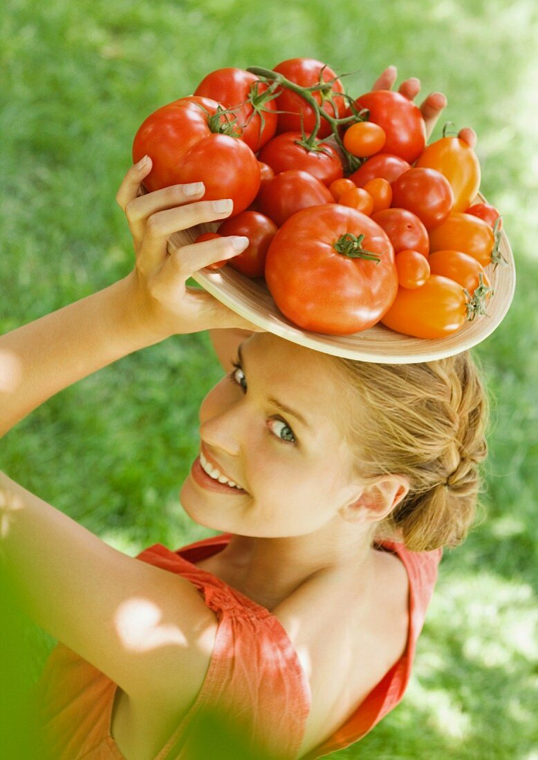Woman holding bowl full of tomatoes on top of head
