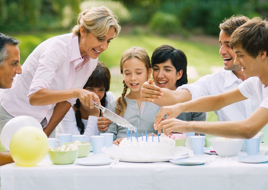 Outdoor birthday party, mature woman cutting birthday cake