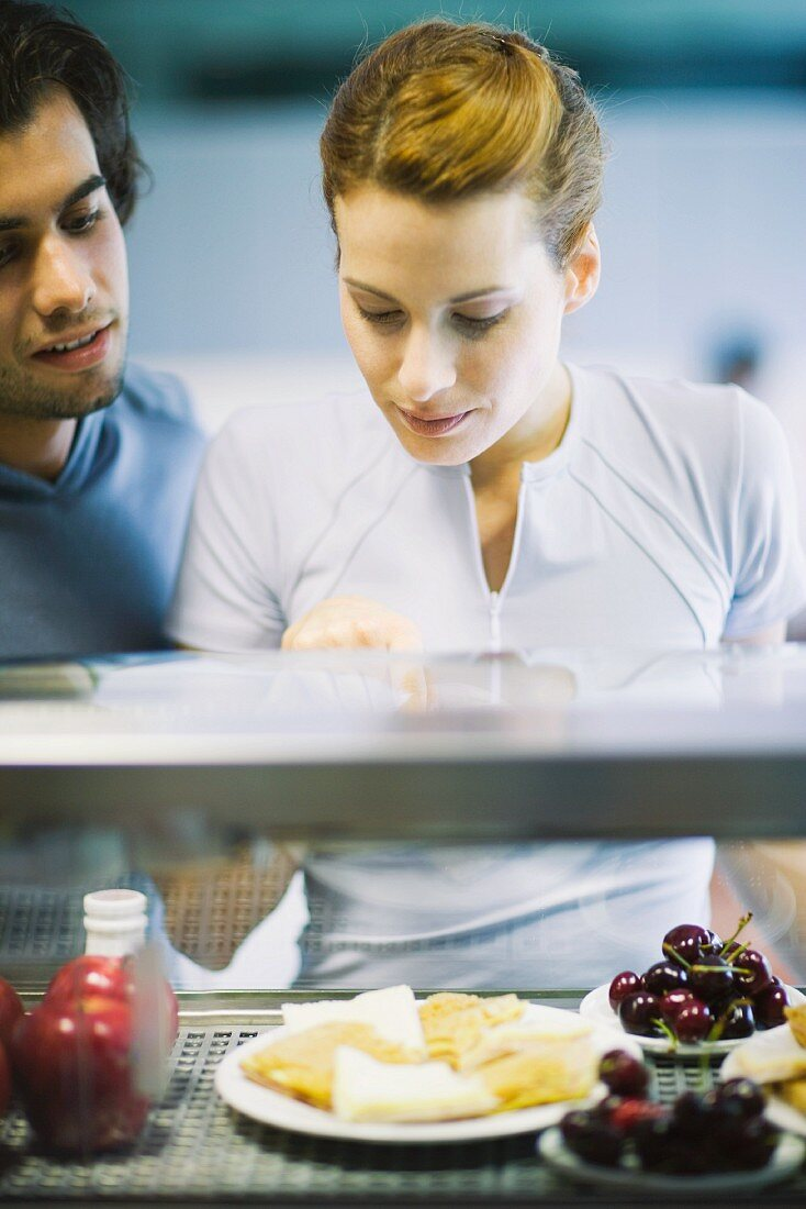 Two young adults standing, choosing healthy snack in cafeteria