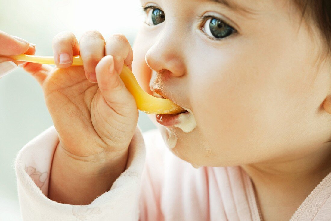 Infant learning to eat with a spoon