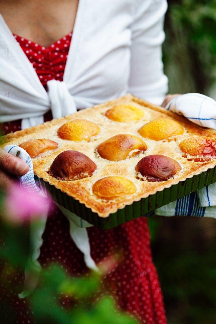 A woman holding a peach pie in a baking tin