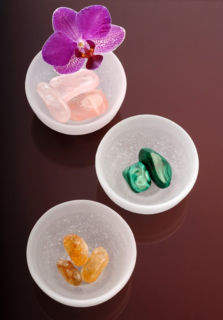 Gemstones in bowls with an orchid flower on a coloured glass surface