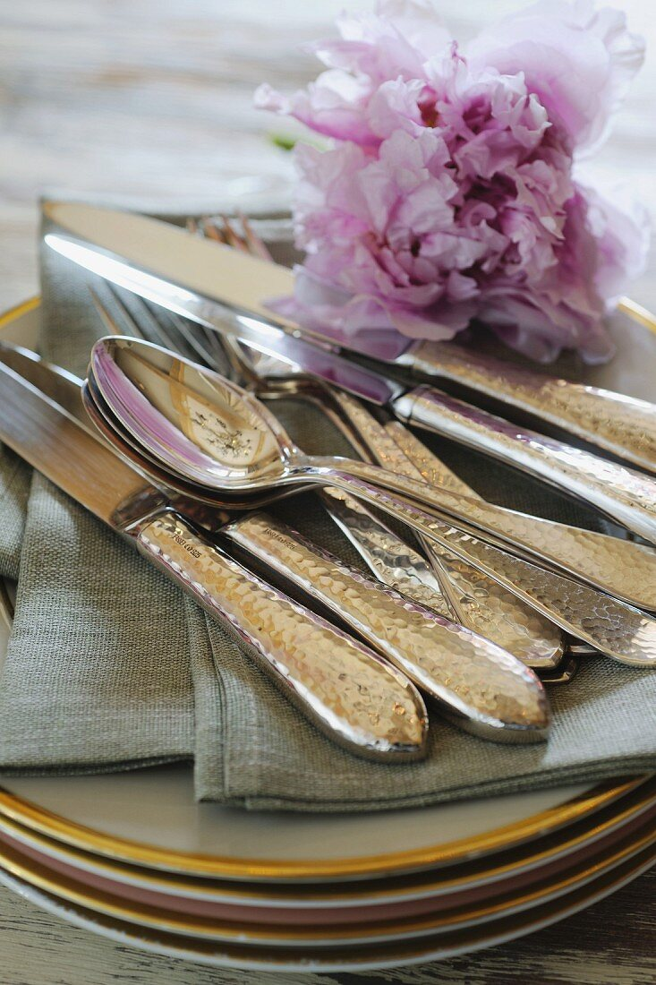 Cutlery and blossom on stack of plates