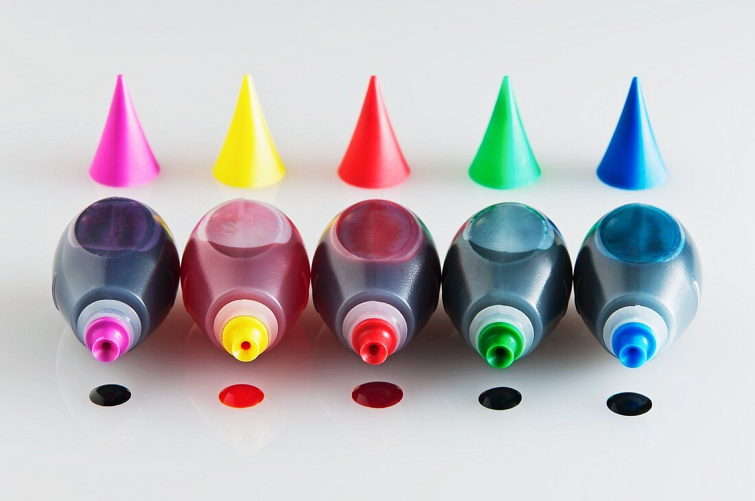 Five Bottles of Food Coloring with Caps Removed and a Drop of Each Color Under Each Bottle
